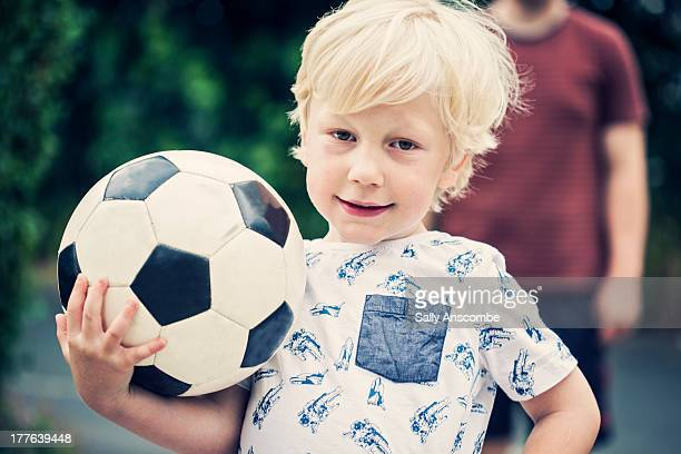 Happy smiling little boy holding a football