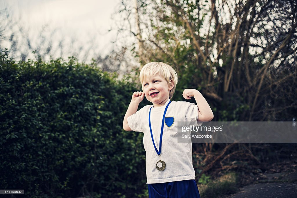 Happy smiling little boy with a medal