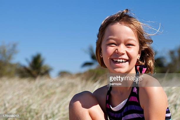 Happy smiling little girl at the beach in sunshine