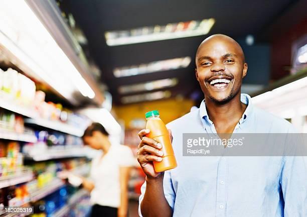 Happy smiling man in supermarket with orange juice