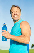 color portrait photo of a happy smiling mature sportsman in his forties wearing a blue tank top and holding a blue water bottle.