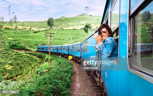 Happy smiling woman looks out from window traveling by train on most picturesque train road in Sri Lanka : Foto de stock