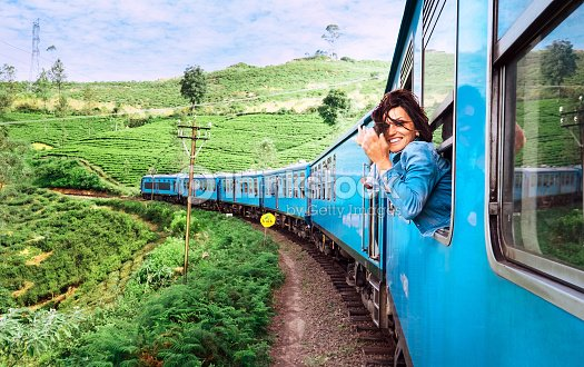 Happy smiling woman looks out from window traveling by train on most picturesque train road in Sri Lanka : Stock Photo