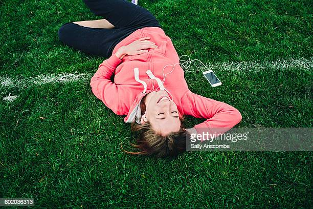 Happy smiling woman lying on the ground