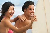 Happy smiling young Asian man and woman, boy and girl, couple on a beach surfing with surfboard