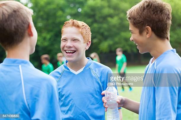 Happy soccer players taking a water break