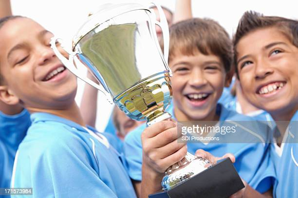 Happy soccer team players celebrating with winning trophy
