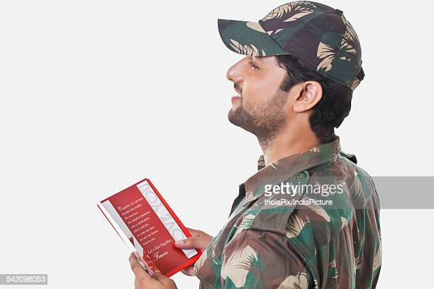 Happy soldier holding greeting card and looking away