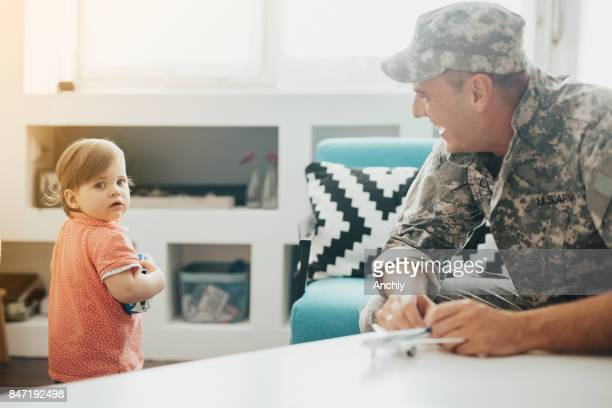 Happy soldier talking to his daughter at home.