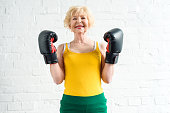 happy sporty senior woman in boxing gloves smiling at camera