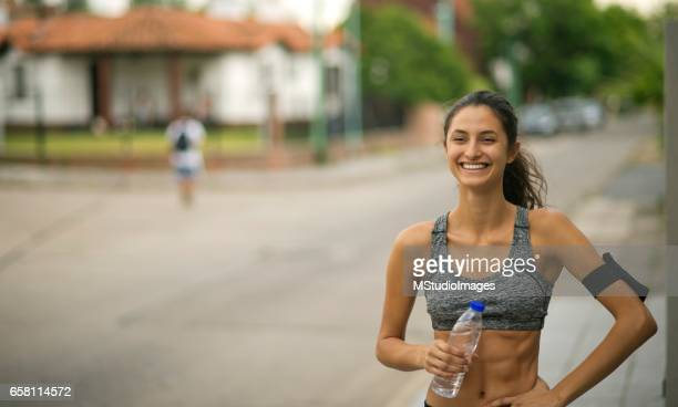 Happy sporty woman holding water