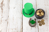 Happy St Patricks Day leprechaun hat with gold coins and lucky charms on vintage style white wood background