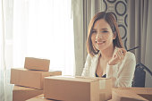 Happy Start up business woman sitting in a desk full of delivery boxes