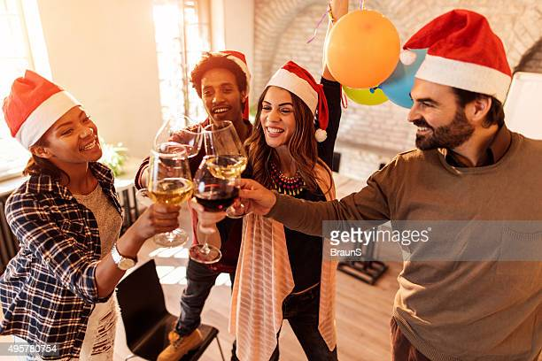 Happy start up team toasting at Christmas office party.