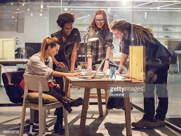 Feliz equipo de inicio usando el ordenador en reunión en la oficina.