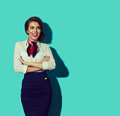Happy stewardess looking right with crossed arms. Beautiful elegant hostess on blue background.
