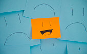 Laughing person surrounded by sad people. Orange sticky note is the odd one out.