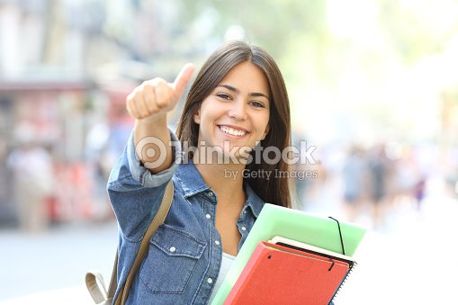 Happy student posing with thumbs up in the street : Stock Photo