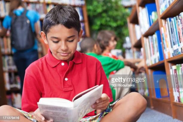 Glückliche Schüler lesen ein Buch in der Schule-Bibliothek