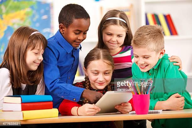 Glückliche Schüler mit digitalen Tablet im Klassenzimmer