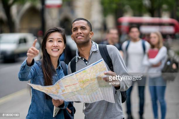 Happy students sightseeing in London and holding a map