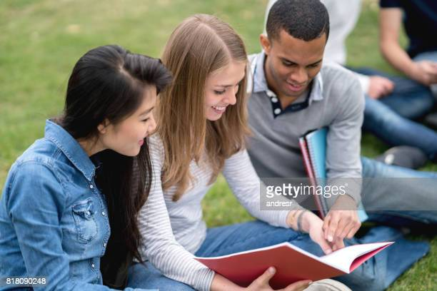 Happy students studying outdoors