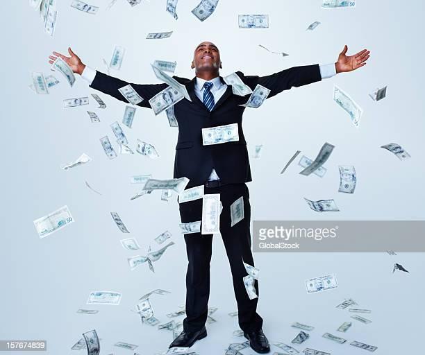 Glückliches erfolgreiches business Mann unter Geld-Regen gegen Weiß