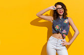 Shouting Girl In Glasses Posing In The Sunlight On Yellow Background