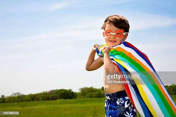Happy Superhero Boy Wearing Towel and Swim Goggles With Copyspace