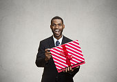 Closeup portrait young happy excited man opening red gift box, pleased, grateful with what he received, isolated black, grey background. Positive human emotions, facial expressions, feelings, attitude