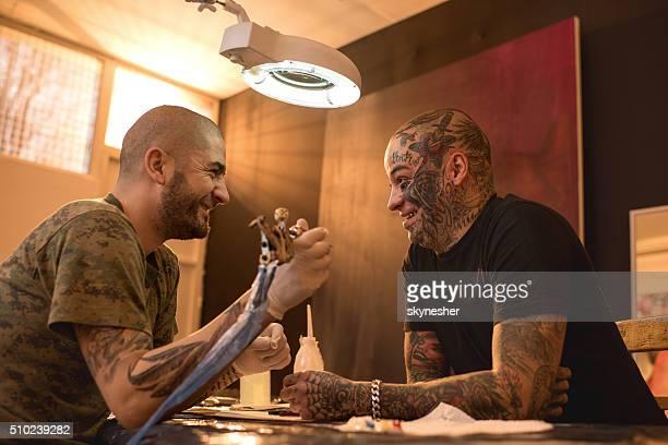 Happy tattoo artist talking to his customer in tattoo studio.