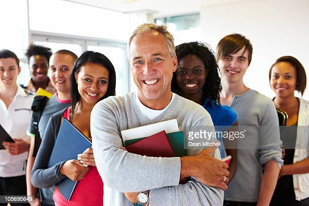happy teacher and students standing in classroom holding books