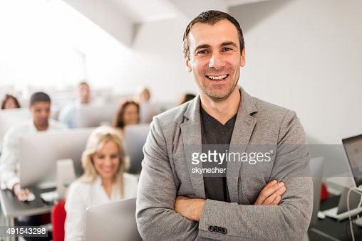 Happy teacher at computer class looking at camera.