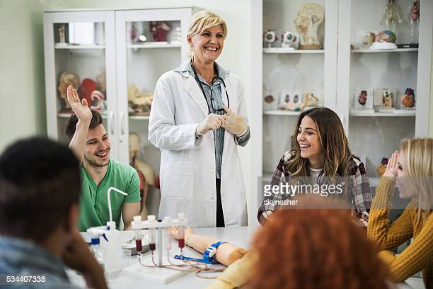 Happy teacher laughing with medical students in the laboratory.