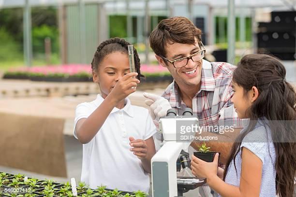 Happy teacher teaches students about botany