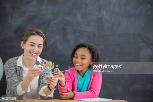 Heureux enseignant utilise un modèle de système solaire dans la classe