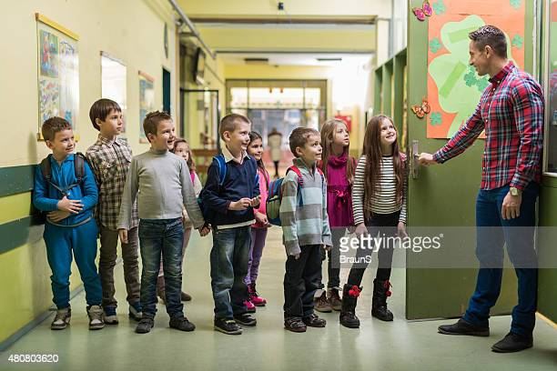 Happy teacher welcoming group of his elementary students.