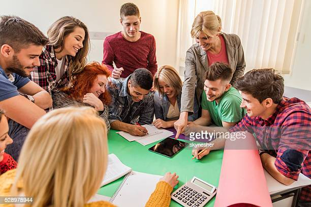 Happy teacher with group of students in the classroom.