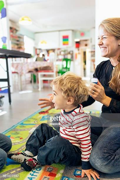 Happy teacher with student looking away in kindergarten