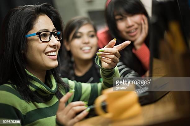 Glückliche junge asiatische Mädchen verschiedener Abstammung mit laptop zusammen.
