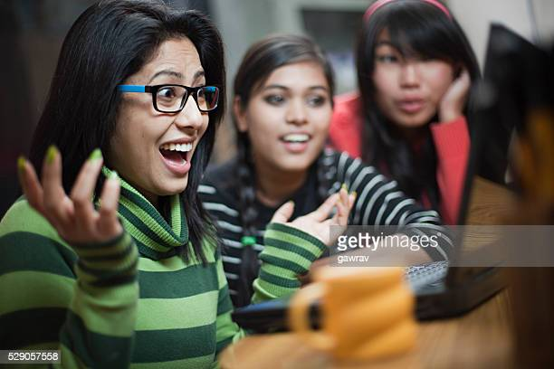 Happy teenage Asian girls of different ethnicity using laptop together.