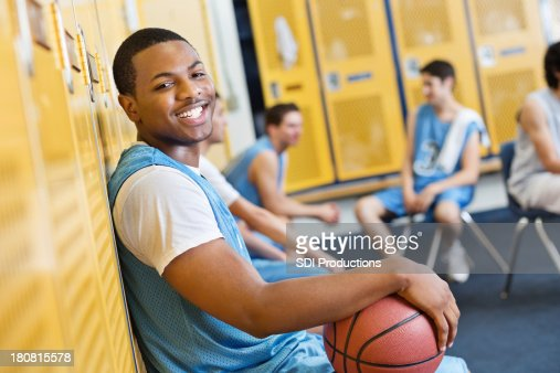 Happy teenage basketball player in high school locker room