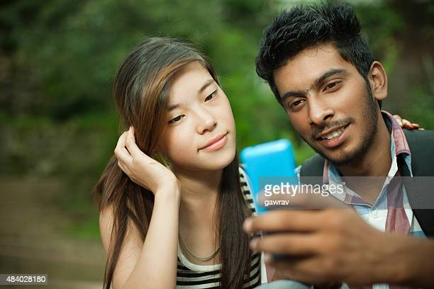 Happy teenage boy and girl of different ethnicity sharing mobilephone.