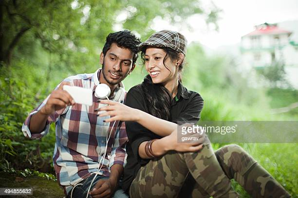 Happy teenage boy and girl of different ethnicity sharing smartphone.
