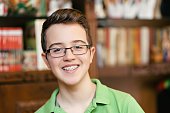 Happy teenage boy with braces and glasses, smiling