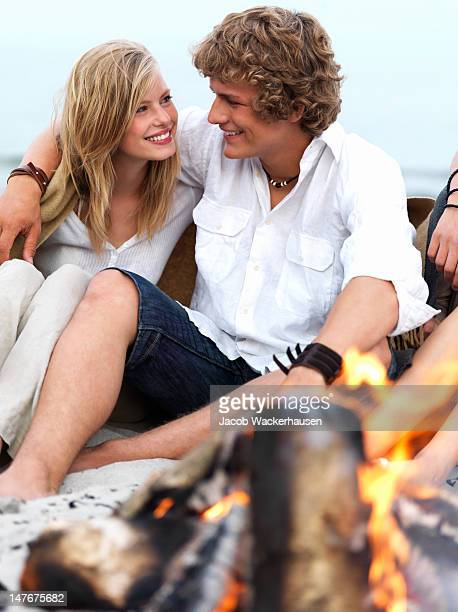 Happy teenage couple sitting together on the beach by bonfire