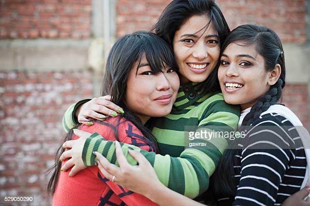 Feliz adolescentes amigas abrazando a otro con sonrisa con dientes.