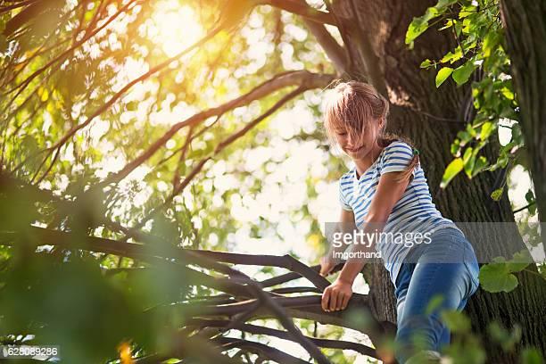 Happy teenage girl climbing tree
