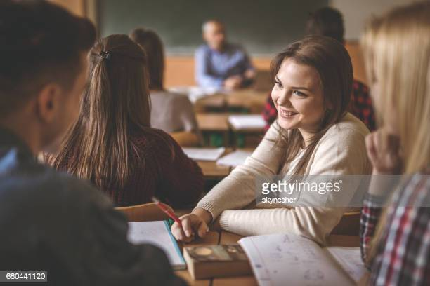 Happy teenage girl taking to a classmate during the class.