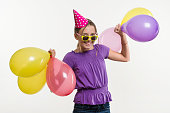 Happy teenage party girl 12-13 years old with balloons. White background